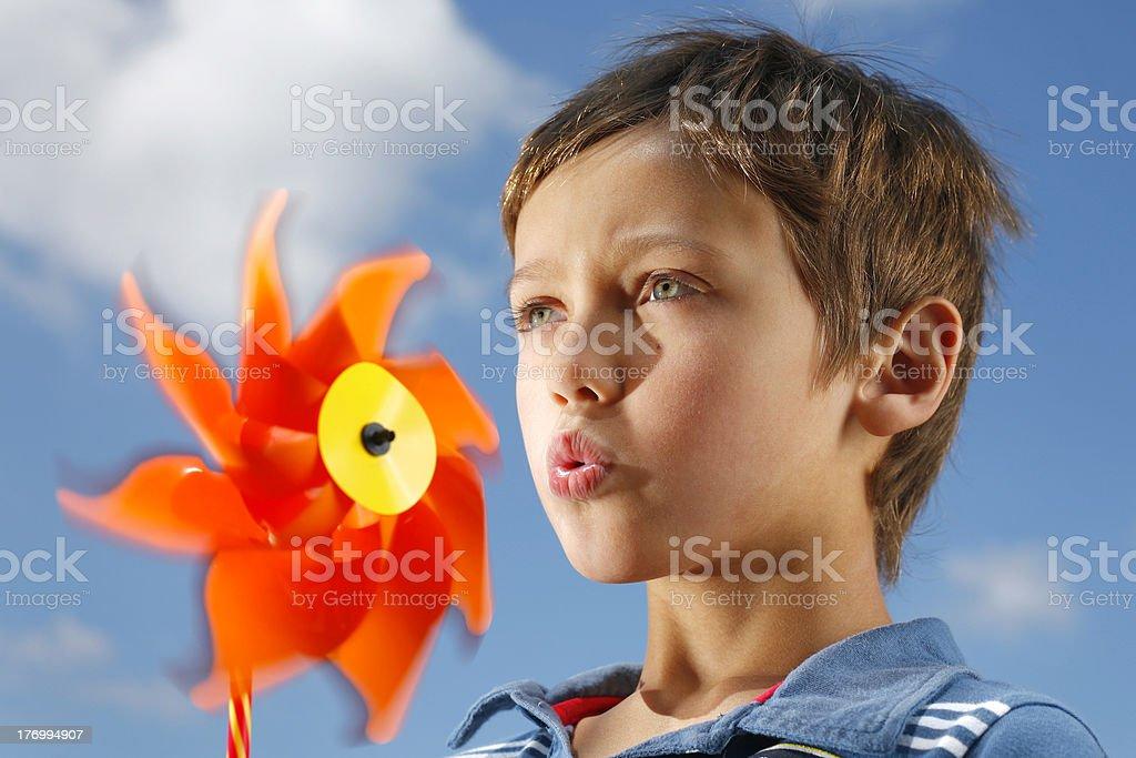 Boy blowing a fan stock photo