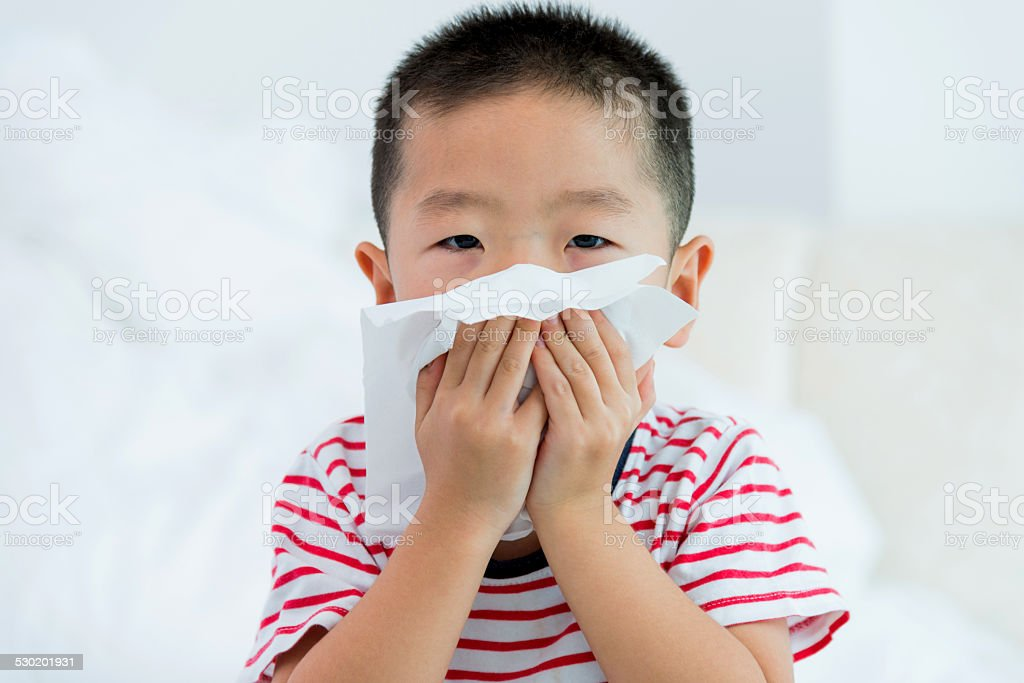 boy blowing nose stock photo