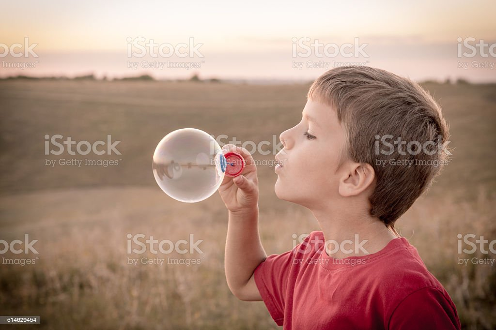 Boy blowing up the soap bubbles stock photo