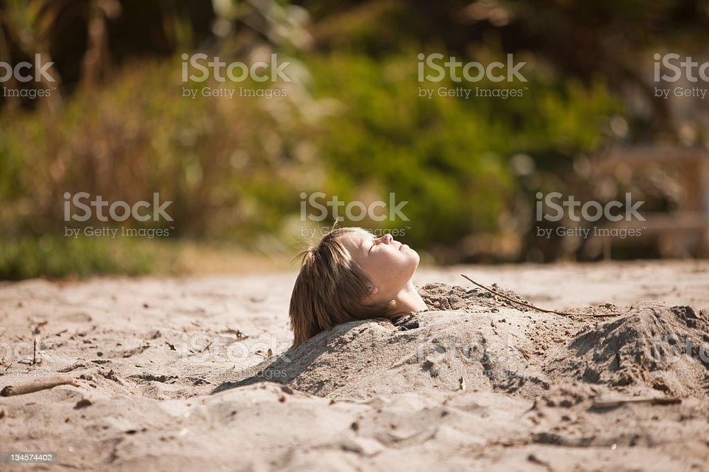 Boy buried up to his neck in the sand stock photo