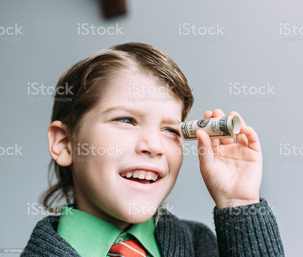 boy businessman looks through small tube from dollar stock photo