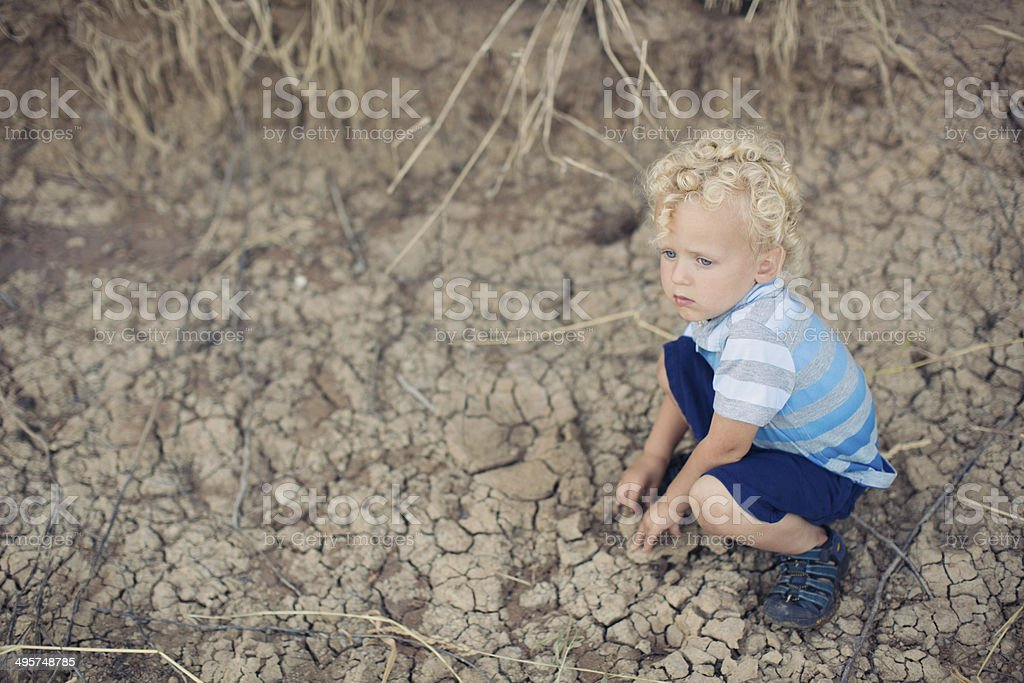 Boy by River Bank stock photo