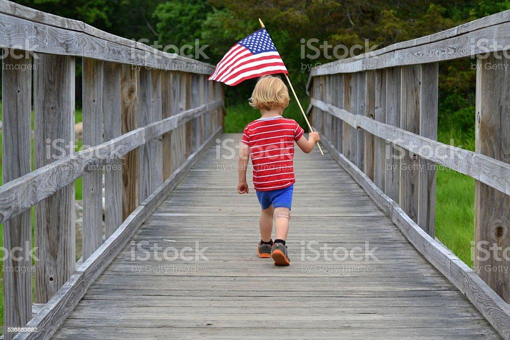 Boy carrying American Flag over bridge stock photo