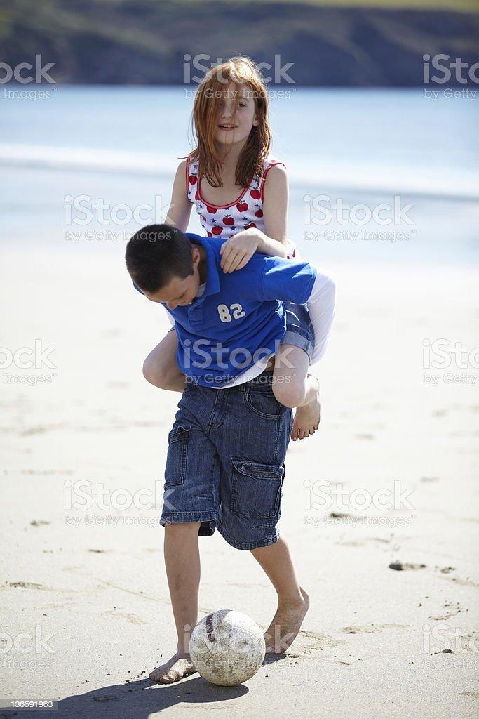 Boy carrying girl piggyback on beach royalty-free stock photo