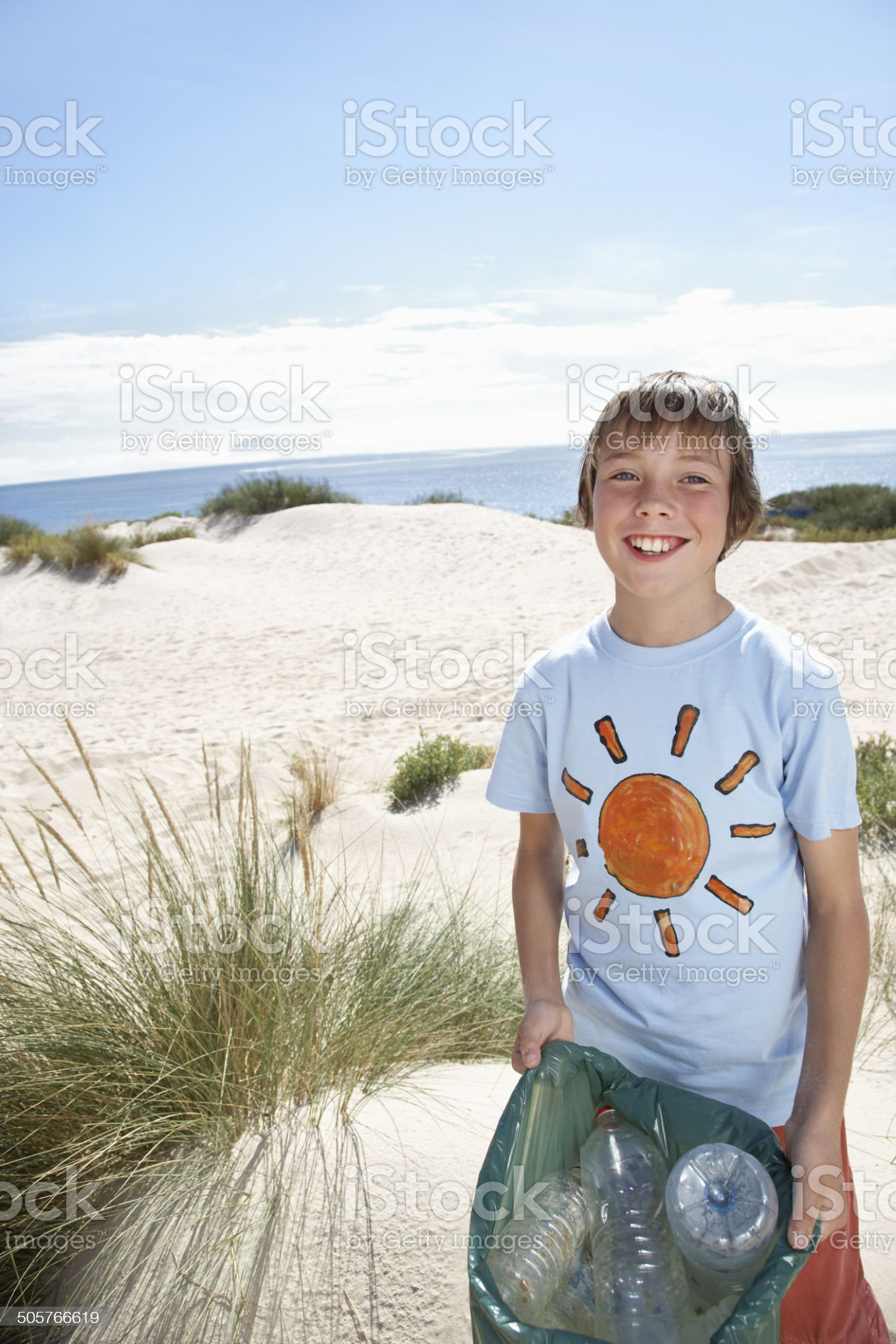 Boy Carrying Plastic Bag Filled With Garbage On Beach royalty-free stock photo