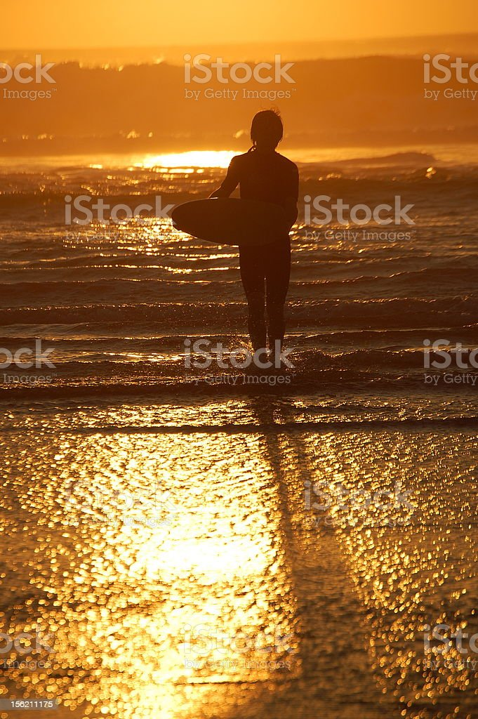 Boy carrying wakeboard in sunset royalty-free stock photo