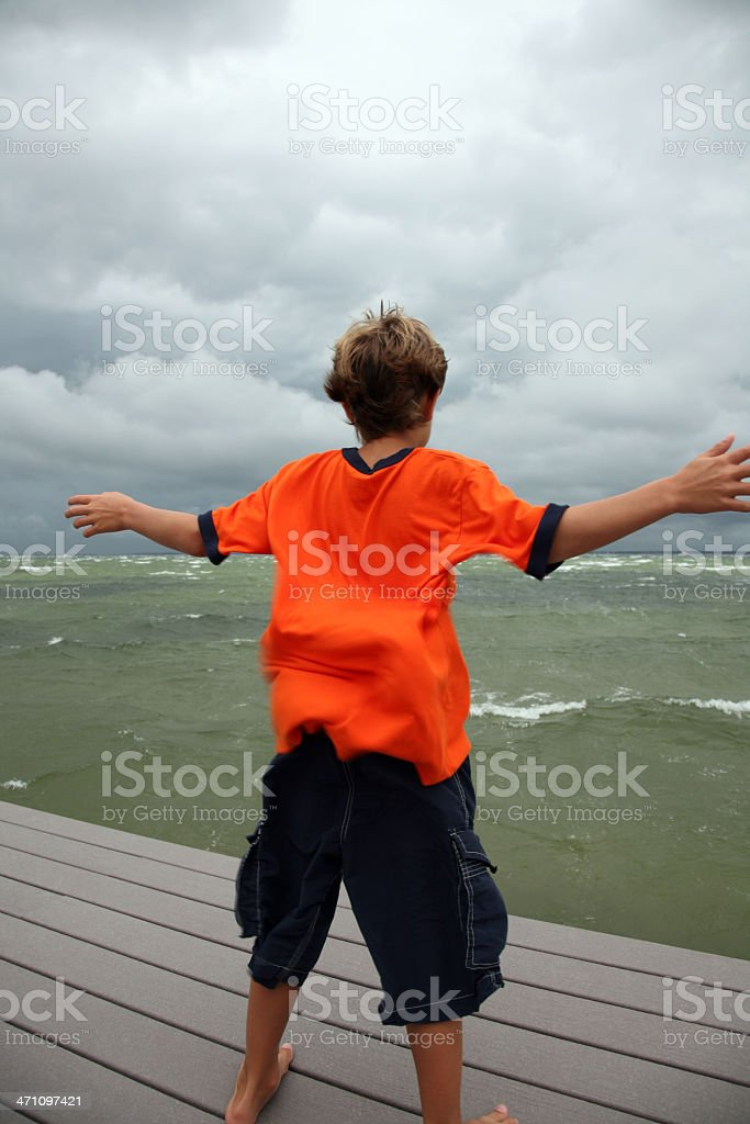 Boy caught in powerful big storm and blowing wind royalty-free stock photo
