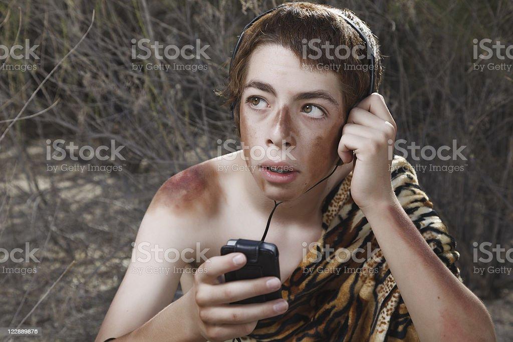 Boy Caveman Wearing Headphones with Music Player stock photo