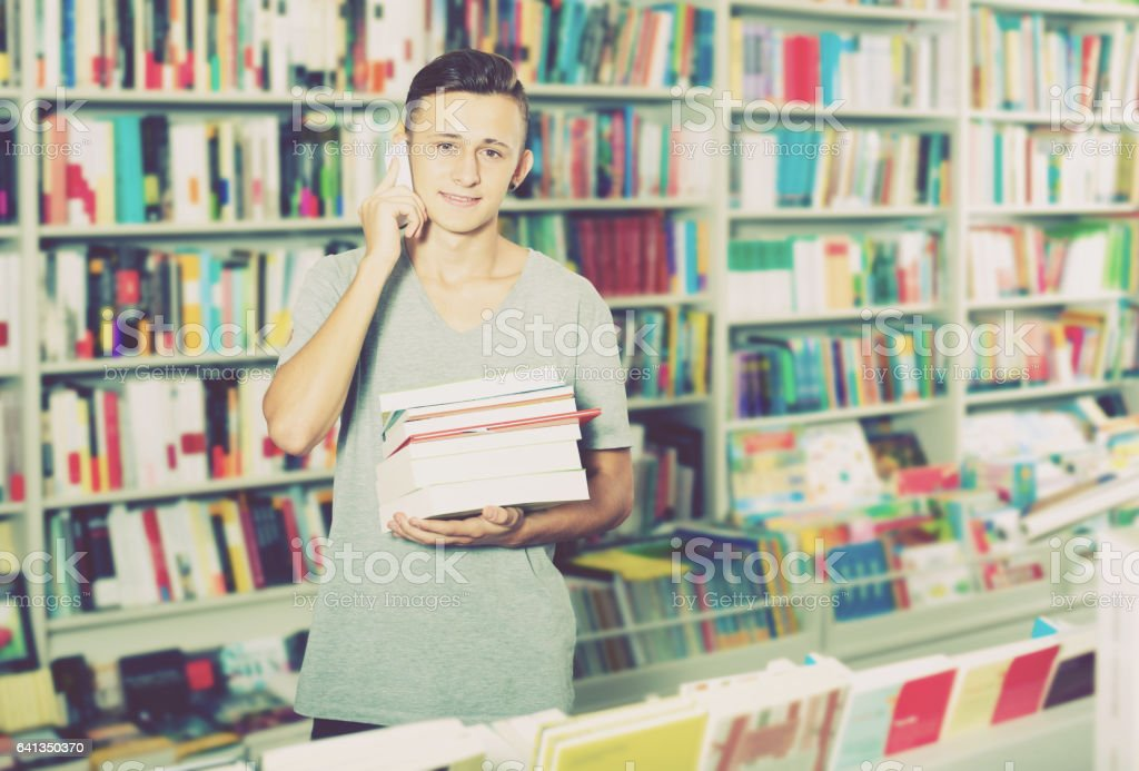 Boy chatting on mobile phone and searching book stock photo