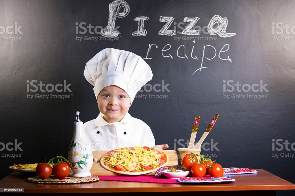 boy chef to cook a pizza stock photo