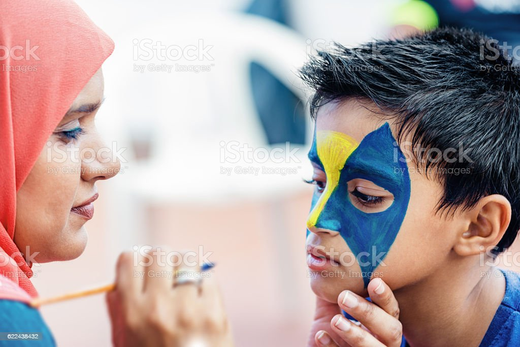 Boy child young having face painted for fun birthday party stock photo