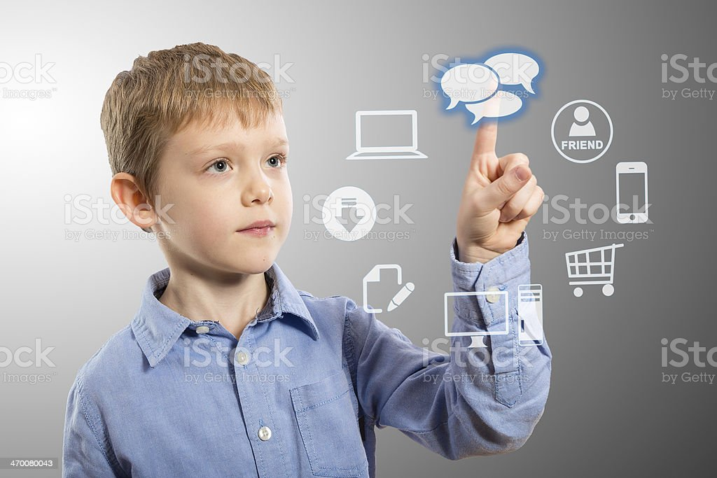 Boy choosing computer applications with left finger stock photo