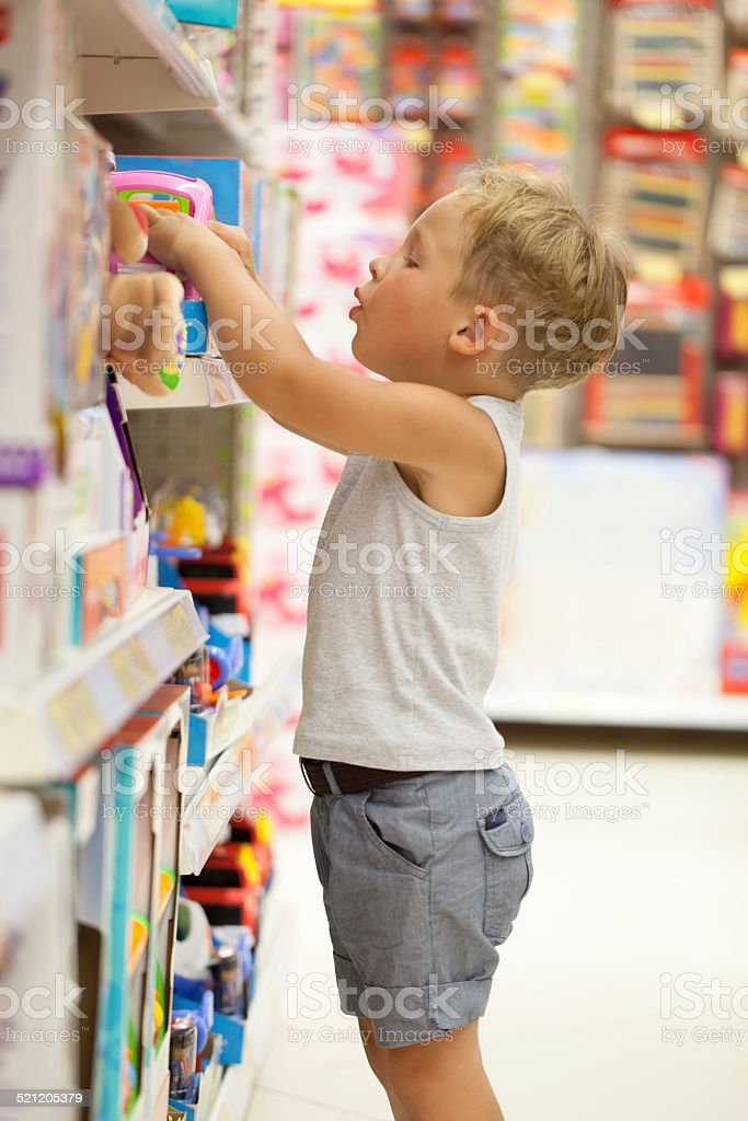 Boy choosing toy in the shop stock photo