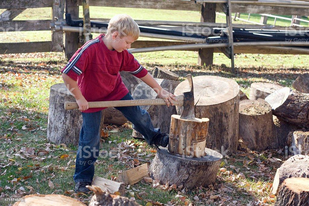 Boy choping wood stock photo