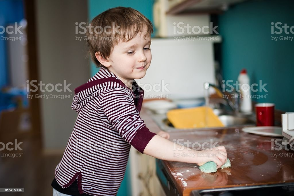 Boy cleaning the kitchen stock photo