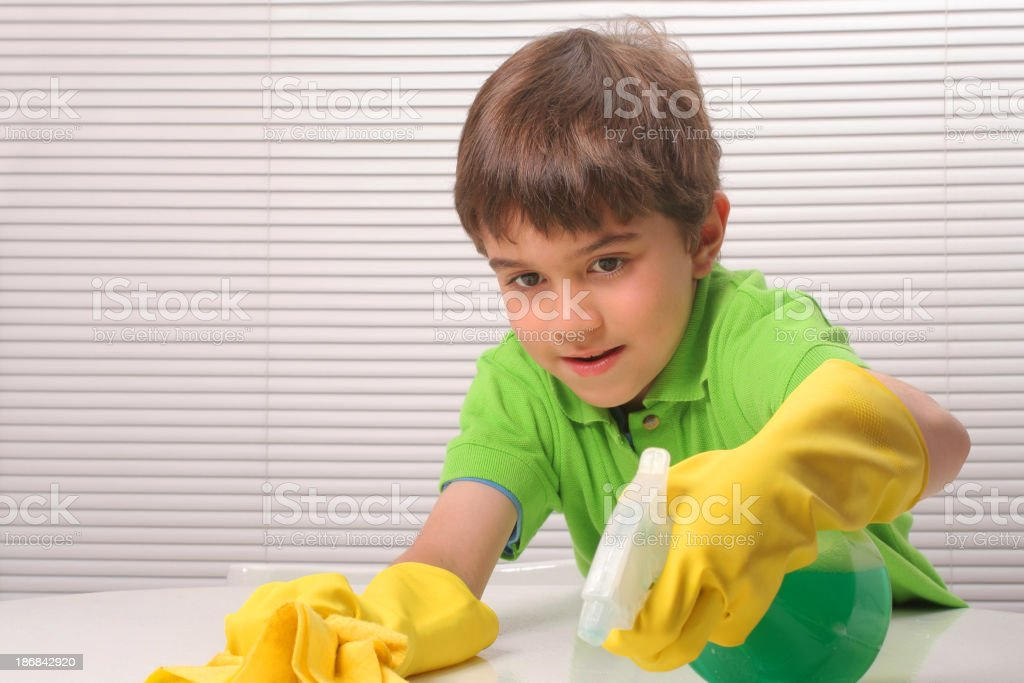 Boy cleaning the table while wearing yellow cleaning gloves royalty-free stock photo