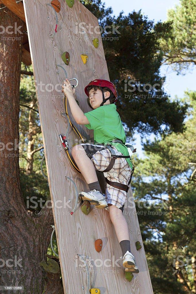 Boy climbing in adventure park stock photo