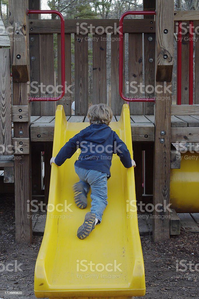 Boy climbing slide royalty-free stock photo