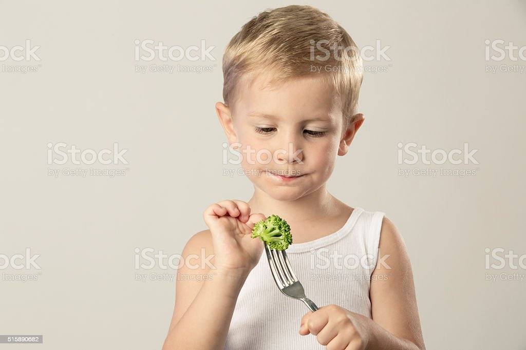 Boy Closing His Mouth with a Fork of Broccoli stock photo