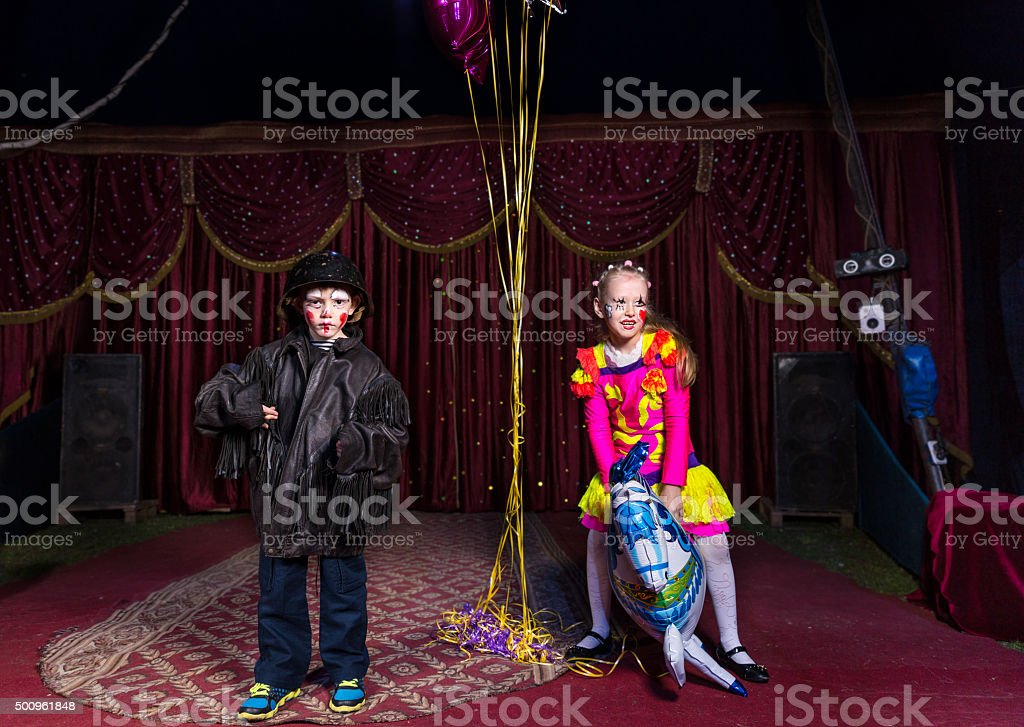 Boy Clown on Stage with Girl Riding Horse Balloon stock photo