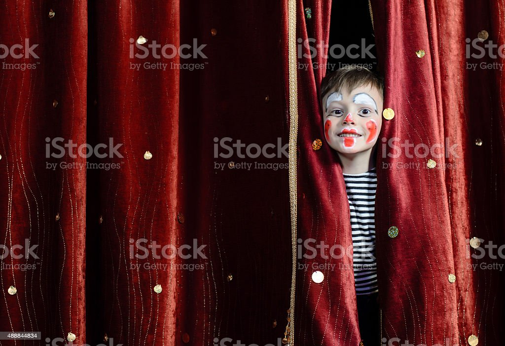 Boy Clown Peering Through Stage Curtains stock photo