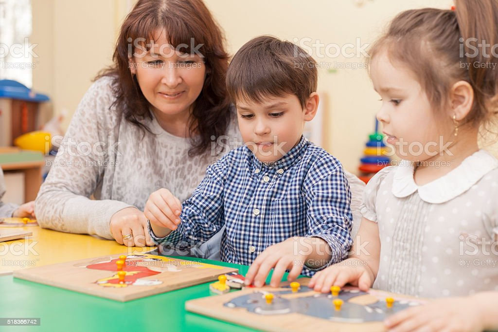 boy collects a puzzle at the table in the classroom stock photo