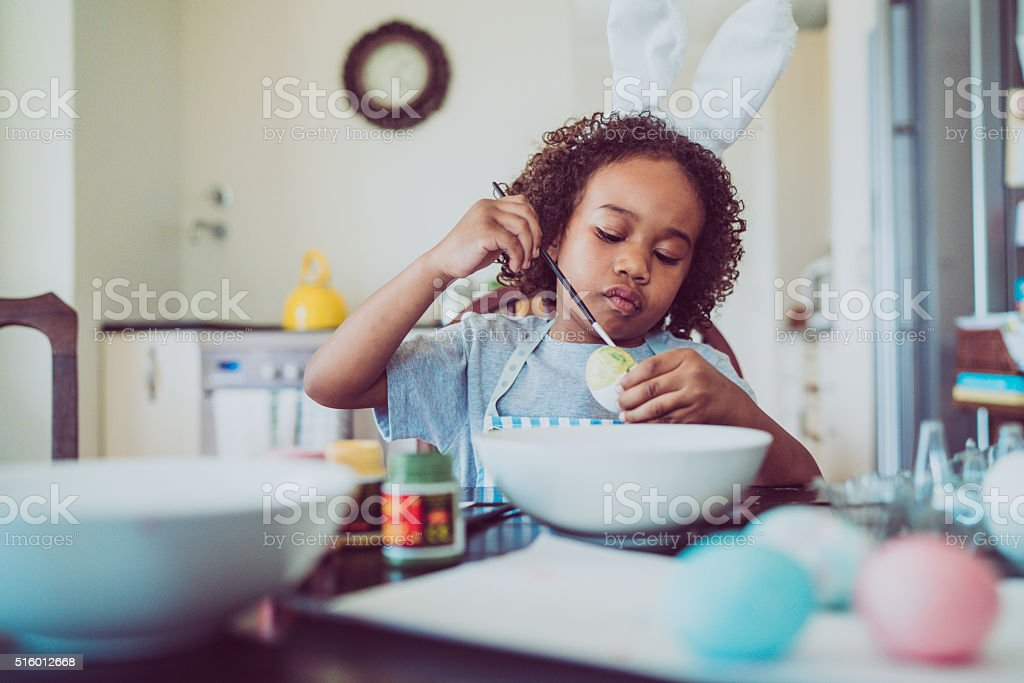 Boy coloring Easter egg at home stock photo