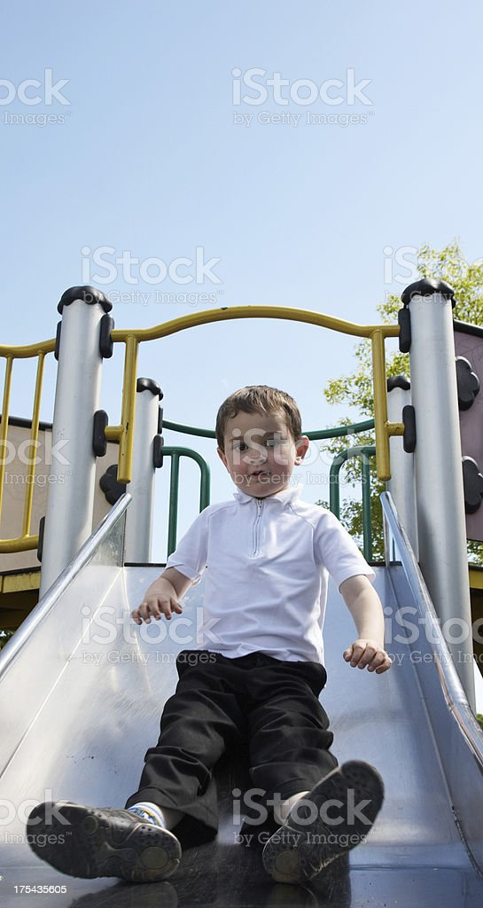 Boy coming down playground slide stock photo
