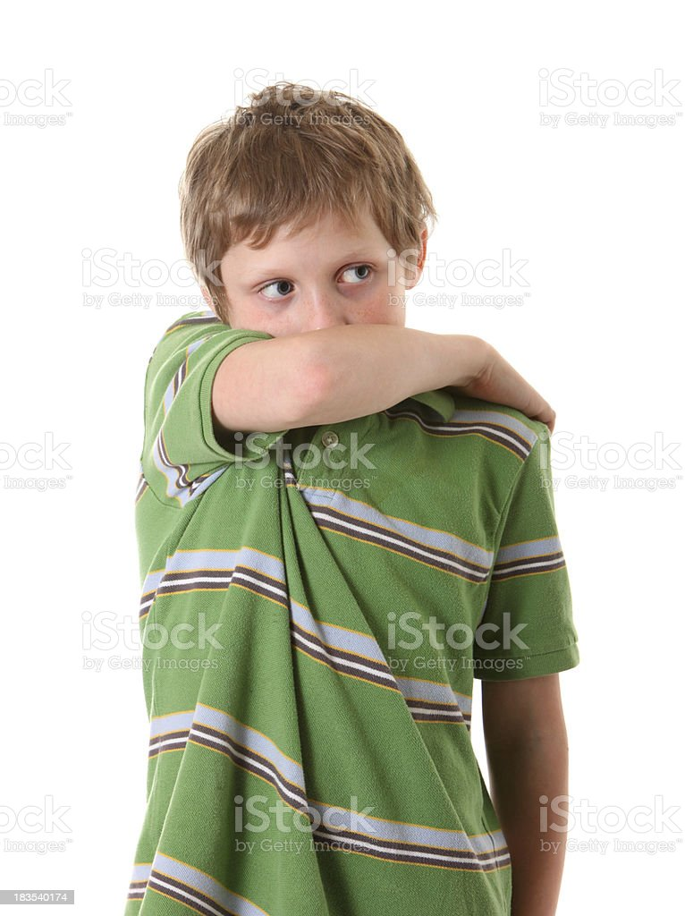 boy coughing into arm looking away royalty-free stock photo