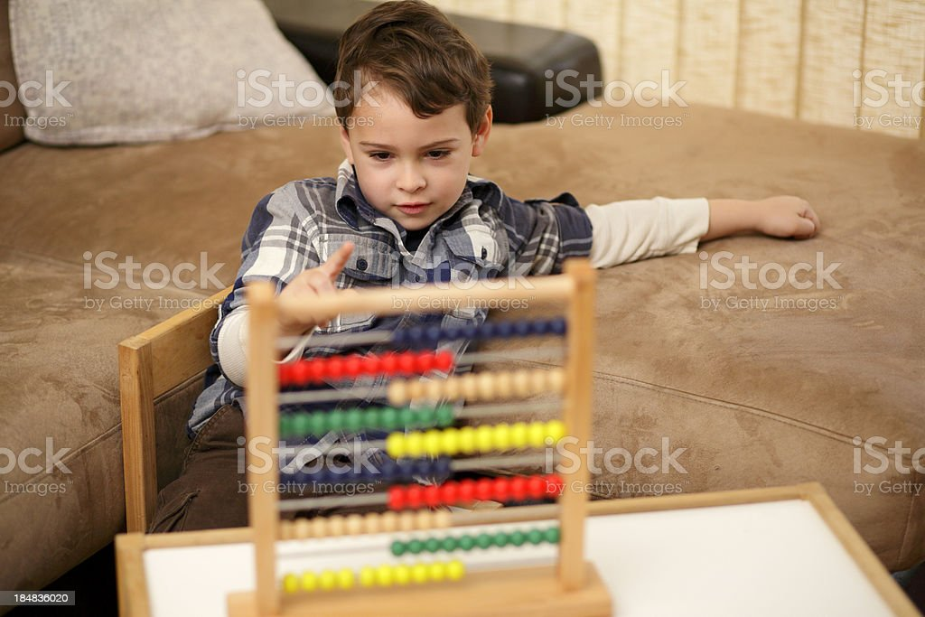 Boy counting beads on his abacus royalty-free stock photo