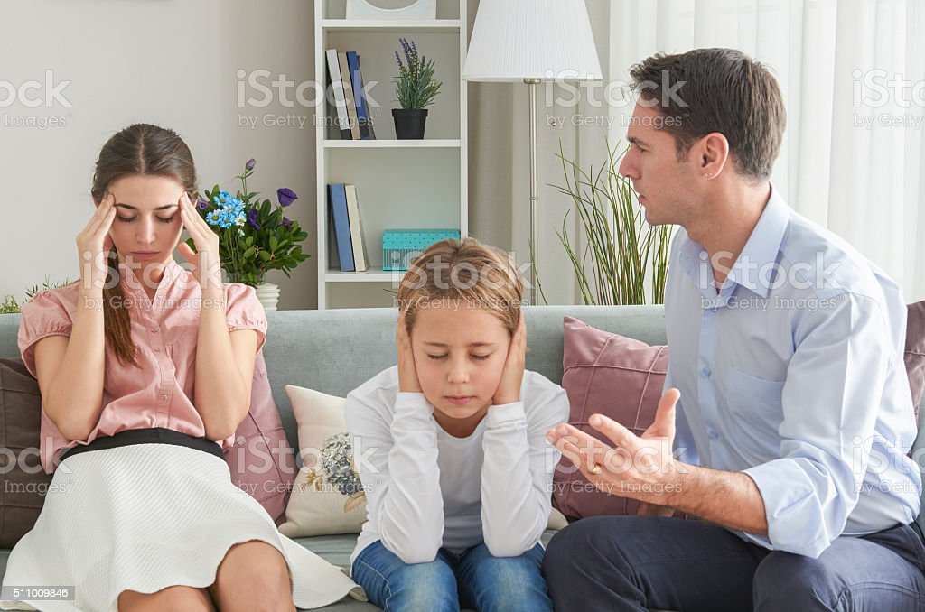 Boy covering ears with hands while her parents arguing stock photo