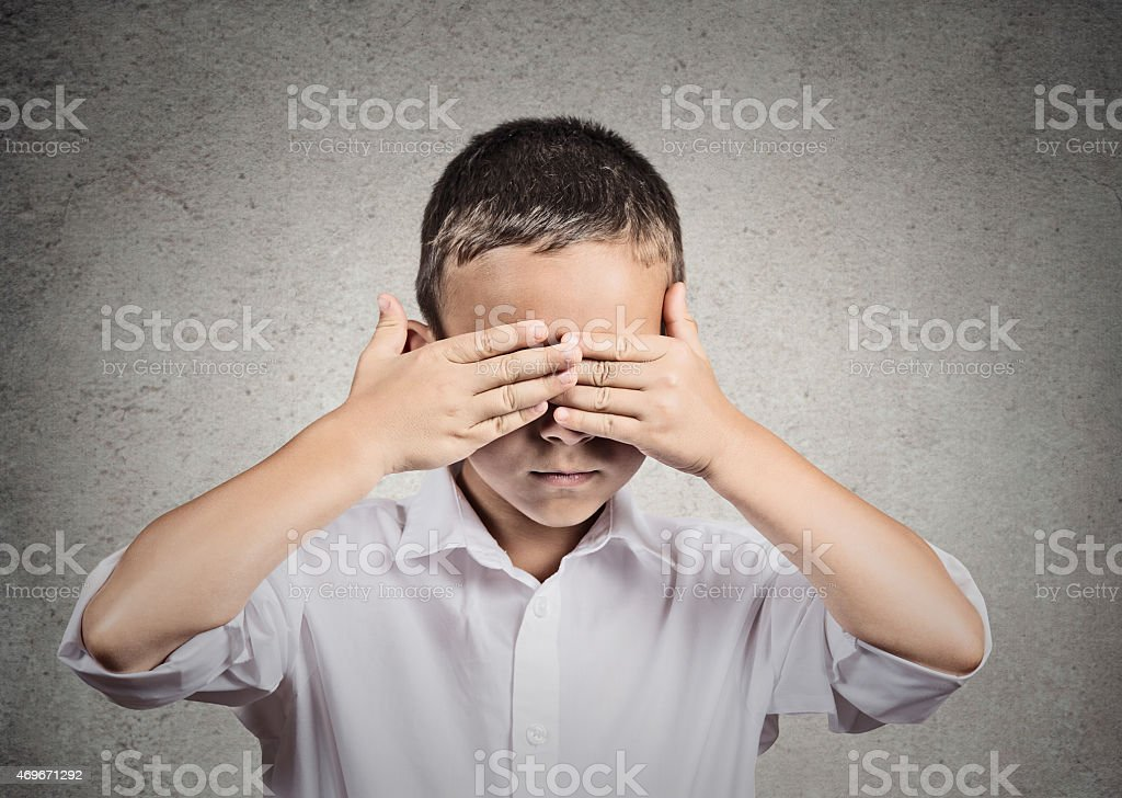 Boy covers his eyes with hands. Hear no evil concept stock photo