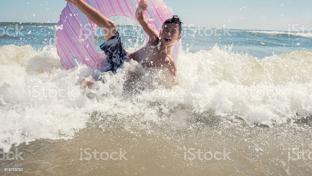 Boy crashes on the waves in the ocean stock photo