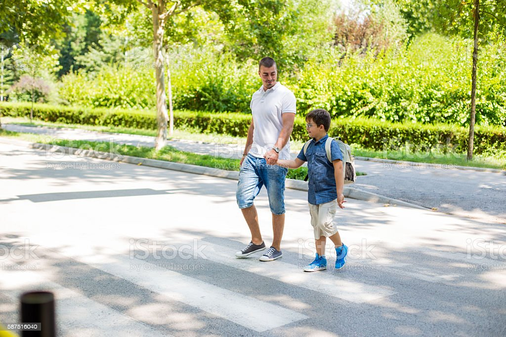 Boy crossing the street with his father stock photo