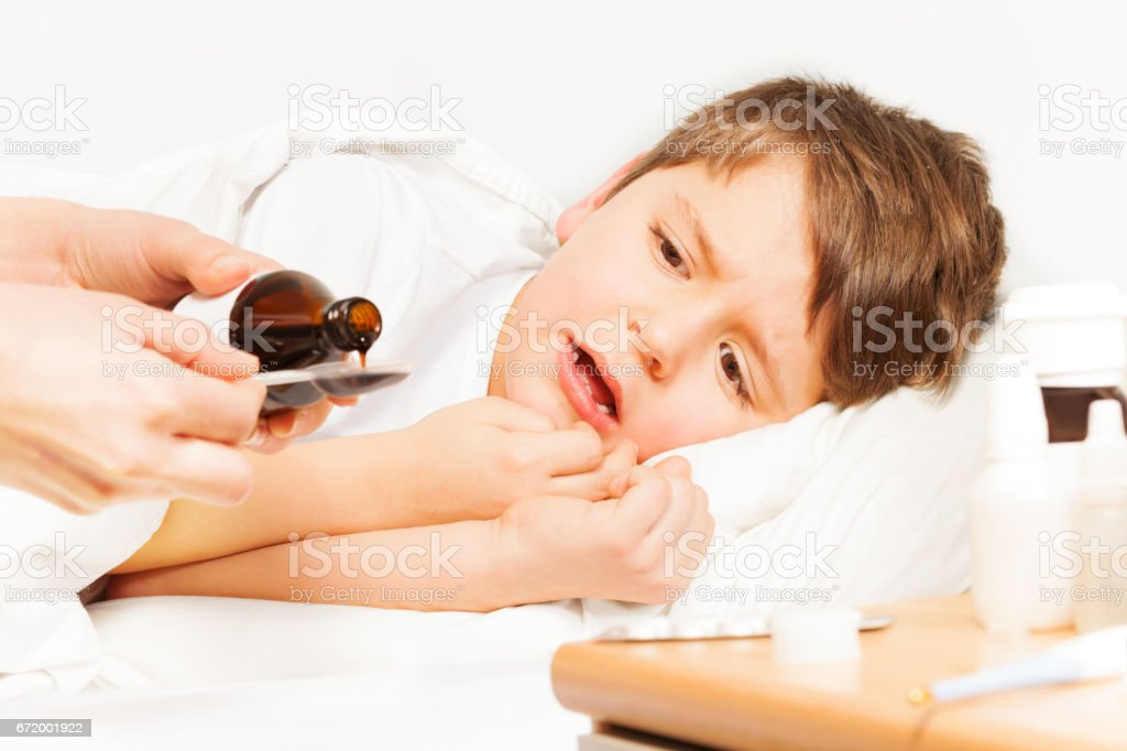 Boy crying while mother pouring coughing syrup stock photo