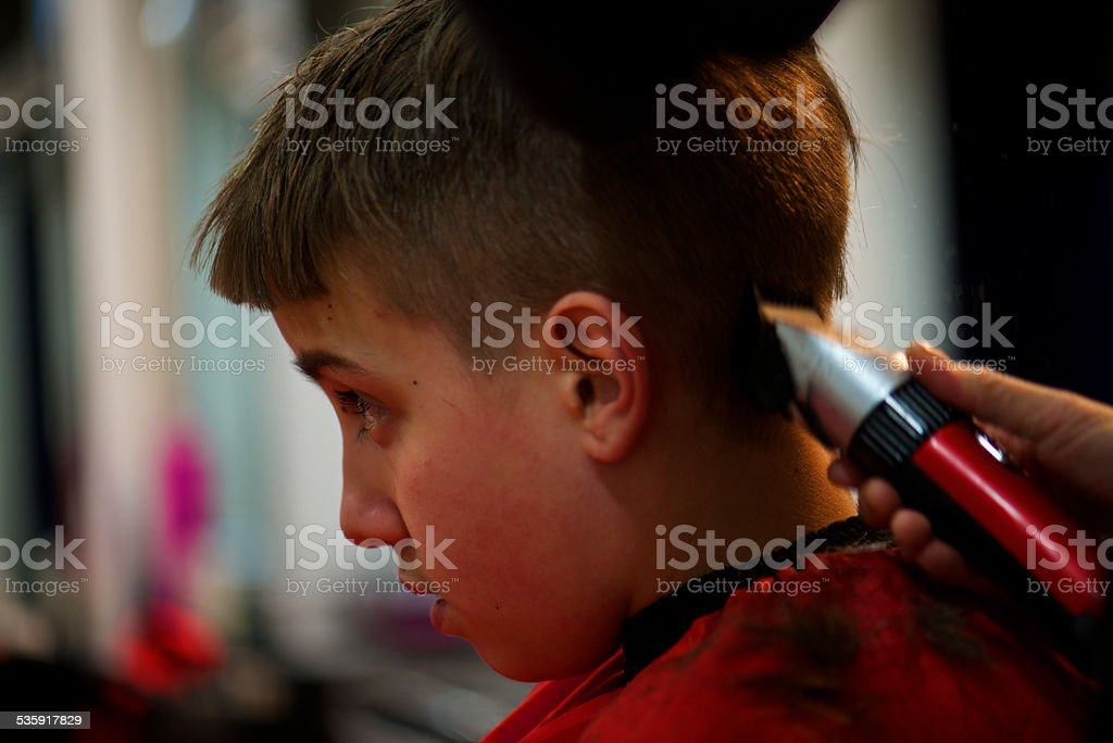 boy cuts her hair with red clippers stock photo