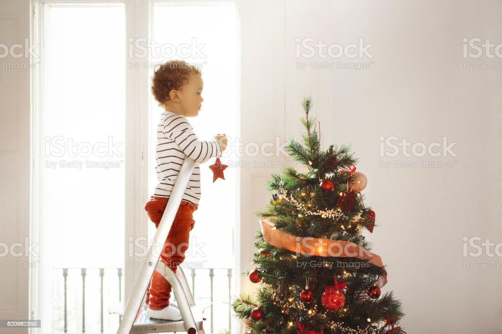 Boy decorating Christmas tree stock photo