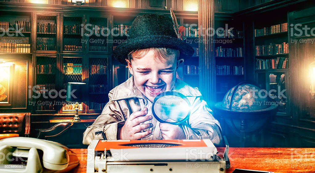 Boy detective with magnifying glass at work stock photo