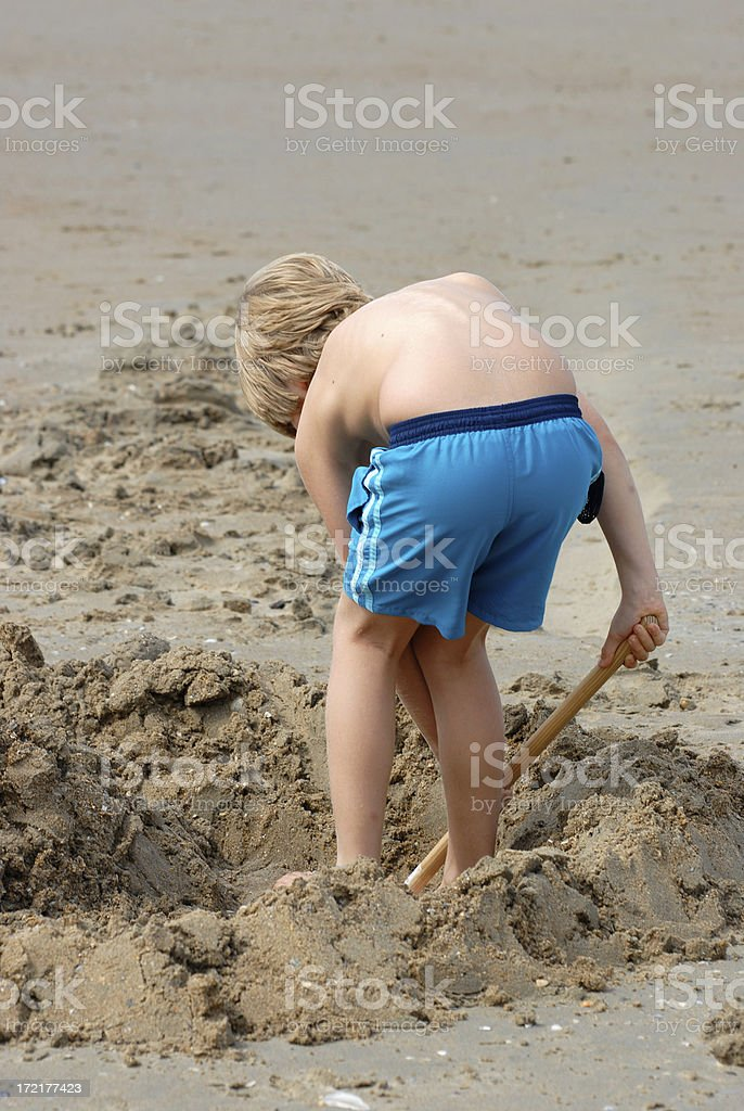 Boy digging a hole in the sand royalty-free stock photo