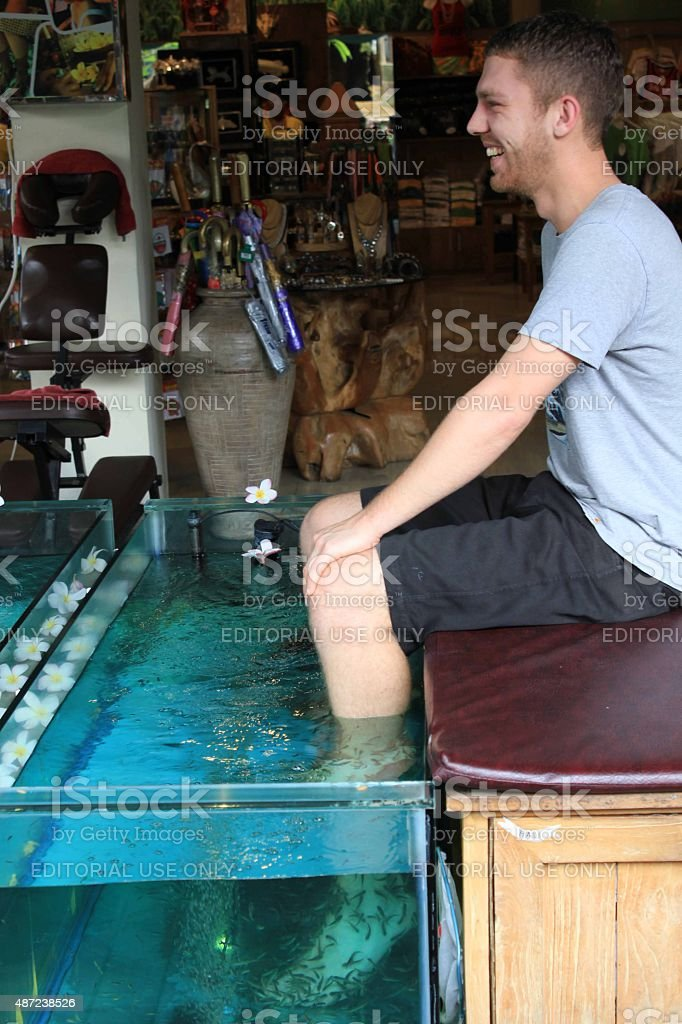 Boy doing feet pedicure with fishes stock photo