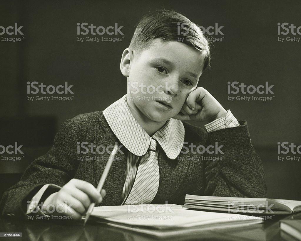 Boy (8-9) doing homework, (B&W), portrait stock photo