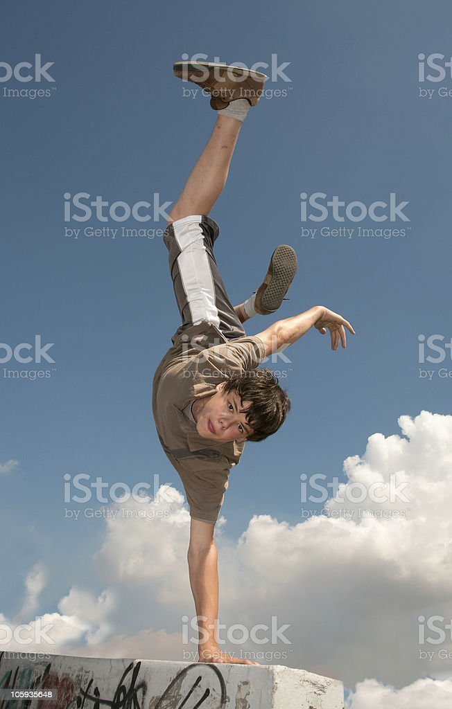 A boy doing parkour off a graffitied wall stock photo