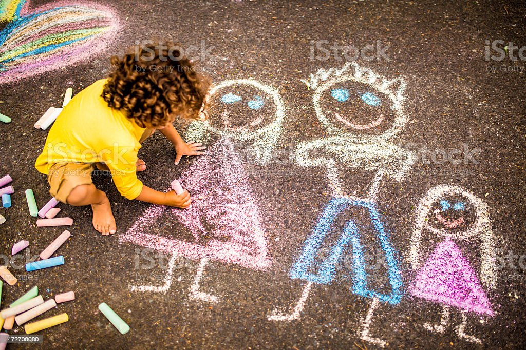 Boy drawing a colourful chalk picture of his family stock photo