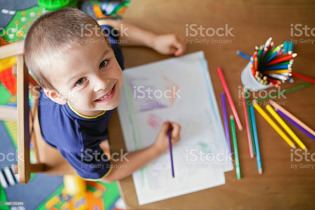 Boy, drawing a picture for mum and dad stock photo