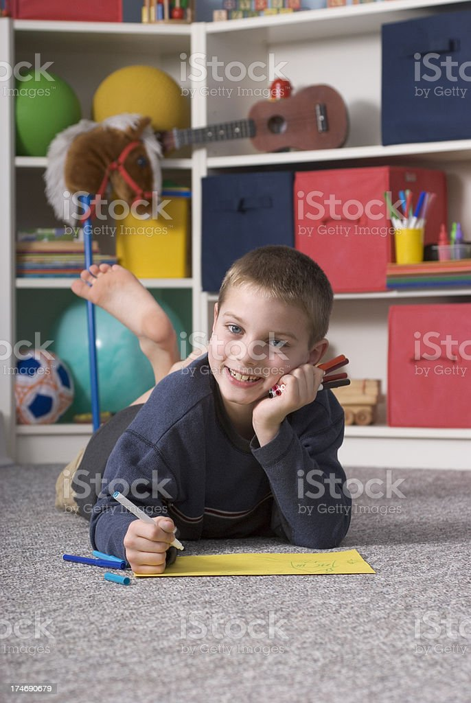 Boy Drawing Inside Playroom, Laying Down, Looking UP Smiling royalty-free stock photo