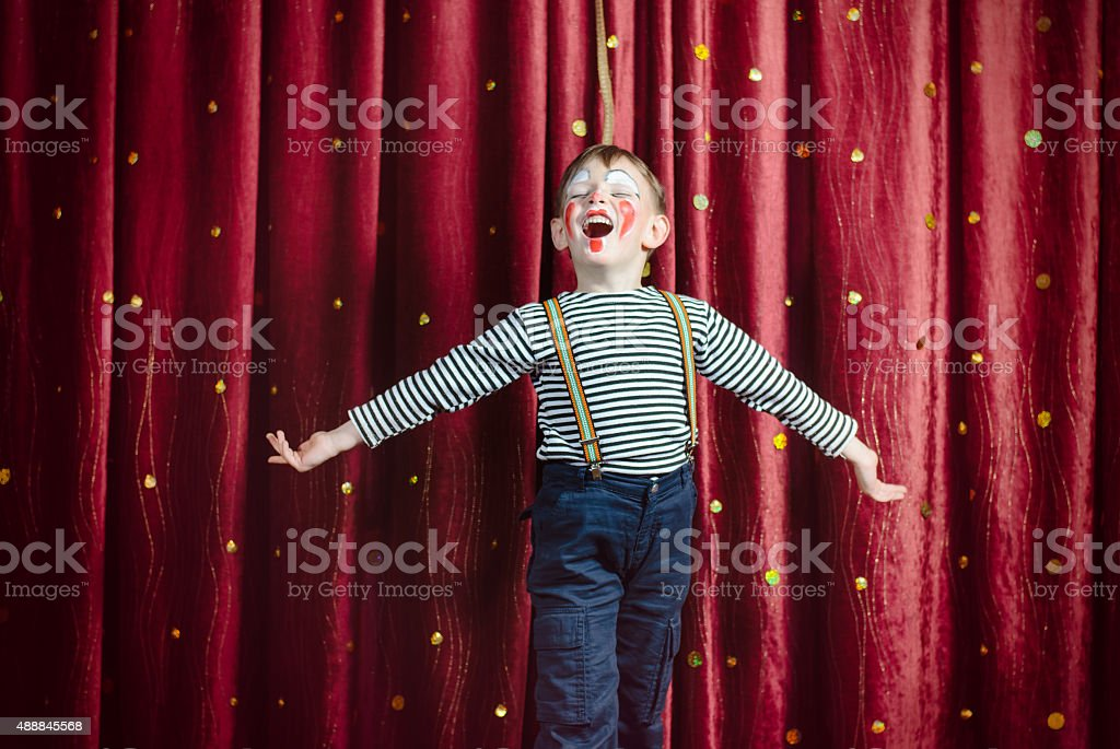 Boy Dressed as Clown Performing on Stage stock photo