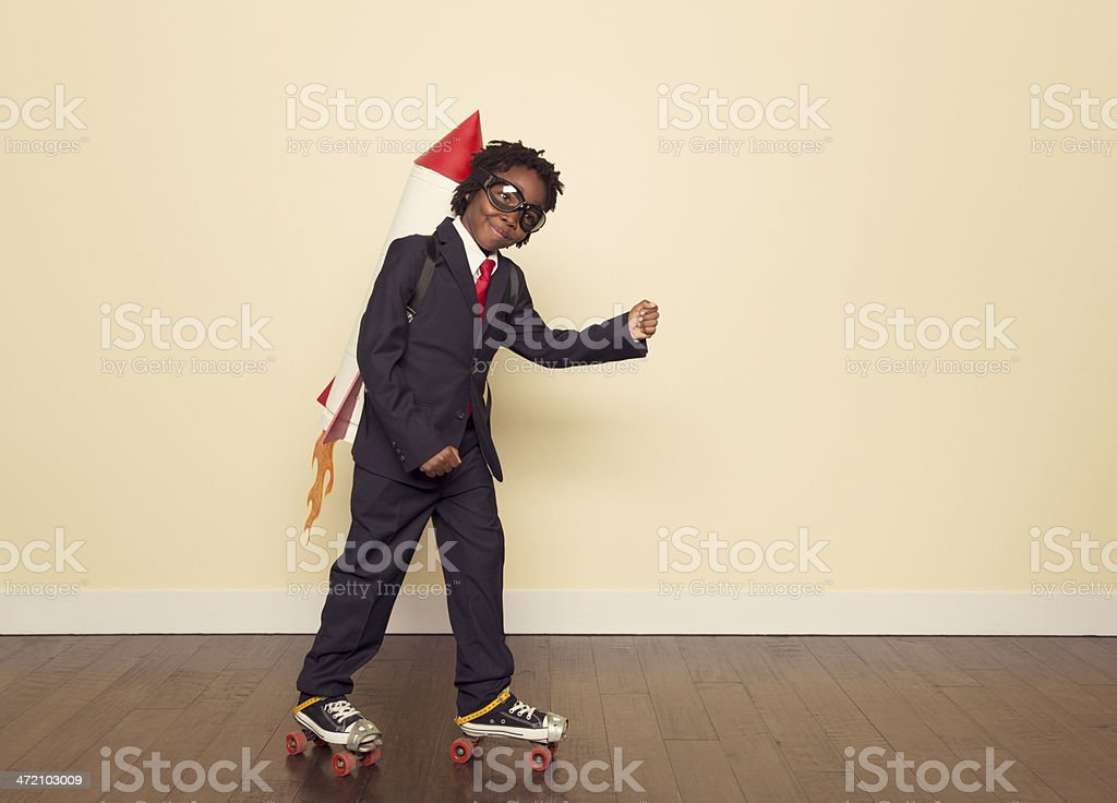 Boy Dressed in Business Suit and Rocket in Studio stock photo