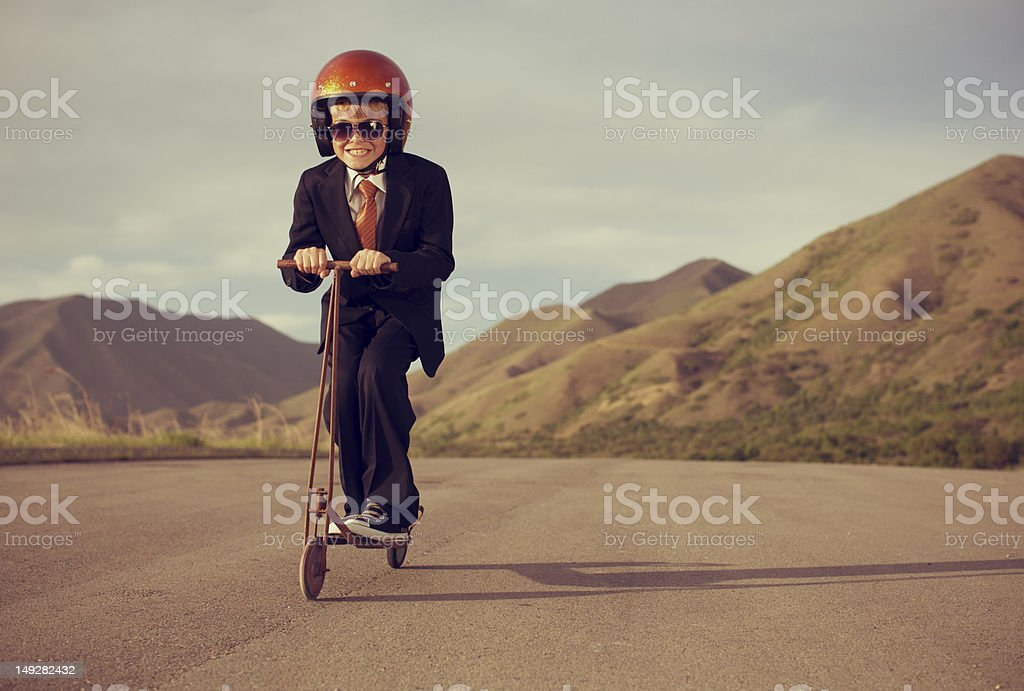 Boy Dressed in Business Suit Riding Retro Scooter stock photo