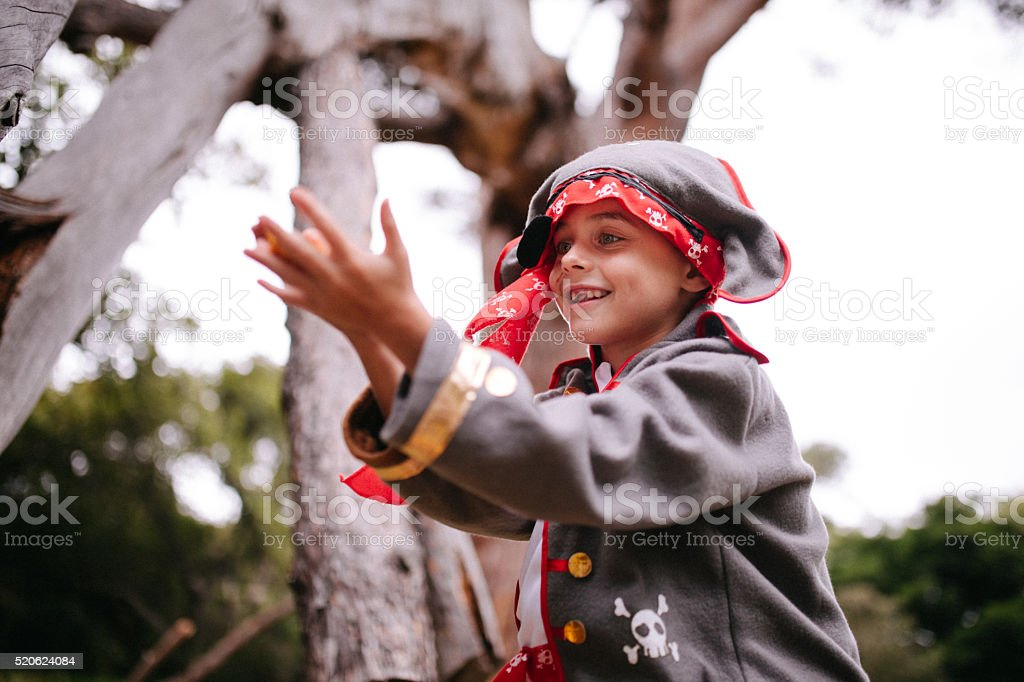 Boy dressed up as pirate with toothy smile in nature stock photo