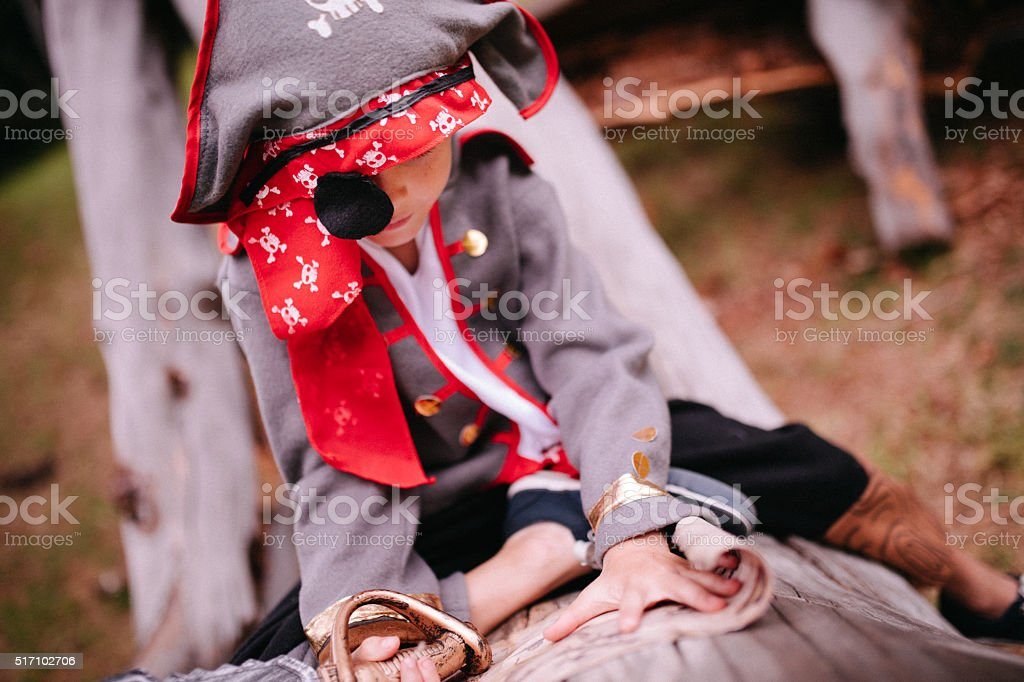 Boy dressing up as pirate sitting on log reading map stock photo